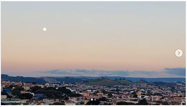 Anoitecer com degradê de azul e rosa com a Lua quase transparente. As nuvens azuladas com seu desenho de montanhas, complementando a paisagem. Lindo!